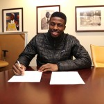 A smiling David Nwaba signs with the Los Angeles Lakers for the remainder of the season. (Photo: Los Angeles Lakers)
