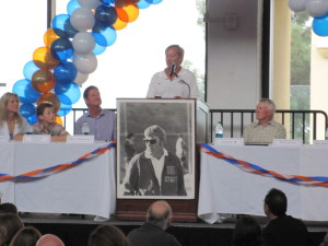 Pepperdine coach Robert Radnoti speaking, with Coach K at right and host (and son) Bill Stimming at left.