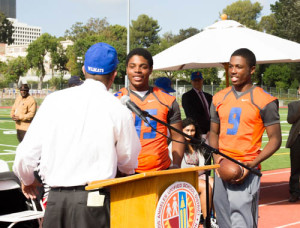 LAUSD Board President Steve Zimmer with Uni footballers Paul Davis (15) and Eugene Ford (9)